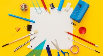Back to school. Colorful composition of school supplies: crayons, scissors, markers, globe, rulers, paints. Notebook in the center. Vibrant color background.
